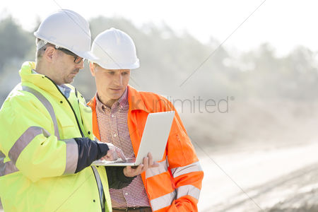 Supervisor : Supervisors using laptop at construction site