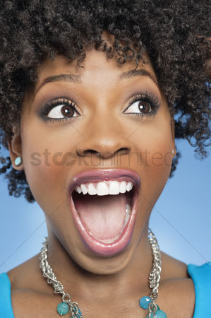 Curly hair : Surprised african american woman looking away with mouth open