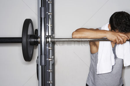 Satisfaction : Sweaty man resting on barbell after workout