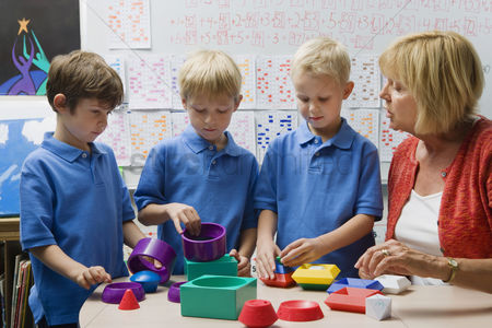 School children : Teacher helping little boys assemble educational puzzle toys