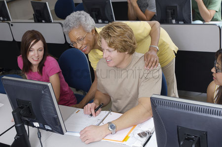 Pupil : Teacher helping two students working in computer classroom