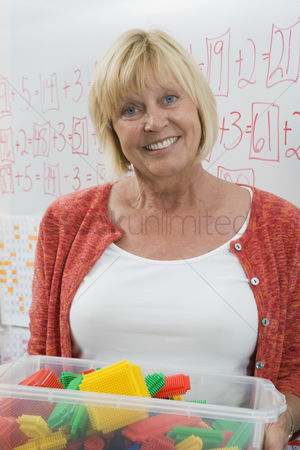 Teacher : Teacher holding a box full of plastic puzzle pieces