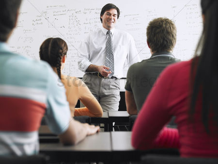 High school : Teacher talking to students in classroom