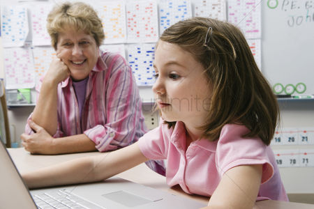 School : Teacher watching schoolgirl use laptop