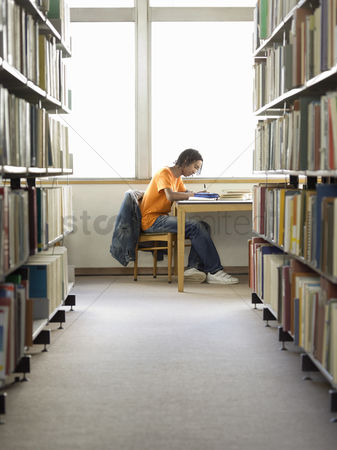 Pupil : Teenage boy doing homework in library