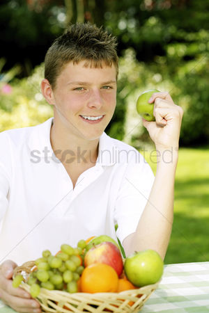 Green grapes : Teenage boy with a basket of fruits