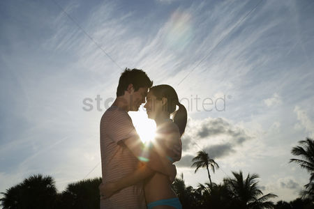 Love : Teenage couple  16-17  embracing on beach at sunset side view