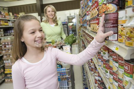 Pink : Teenage girl choosing products from supermarket shelf