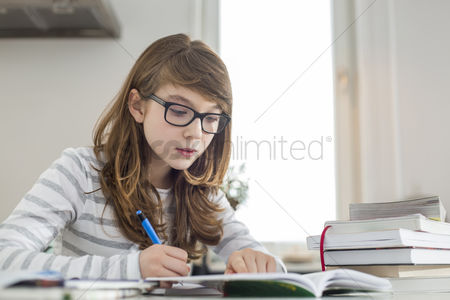 Learning : Teenage girl doing homework at table