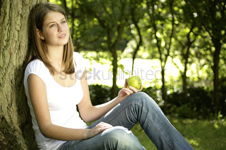 Thought : Teenage girl holding green apple while leaning against tree