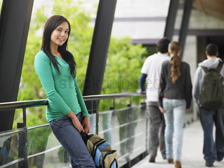 Appearance : Teenage girl leaning against railing in corridor portrait