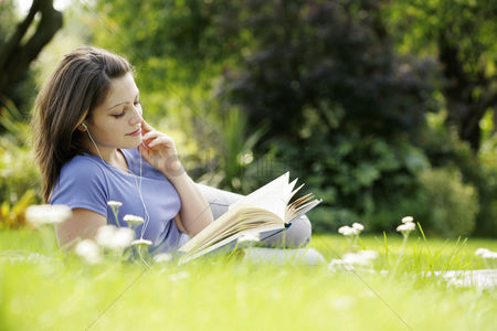 Outdoor : Teenage girl listening to music while reading book