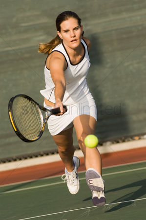 Match : Tennis player reaching to hit tennis ball on tennis court