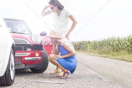 Worry : Tensed women looking at damaged cars on road against clear sky