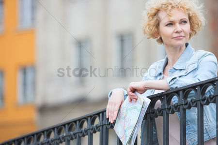 On the road : Thoughtful middle-aged woman holding map while leaning on railing