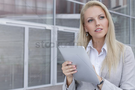 Contemplation : Thoughtful young businesswoman using digital tablet while looking away against office building