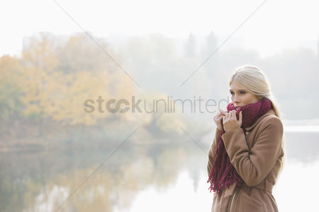 Three quarter length : Thoughtful young woman wearing muffler at lakeside in park