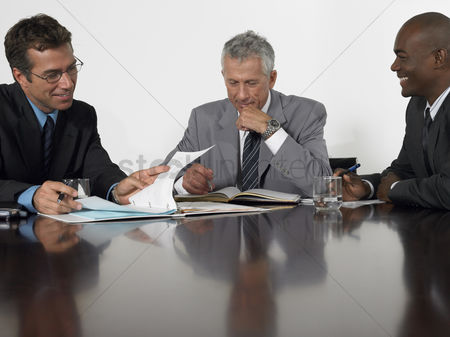 Smiling : Three businessmen in conference meeting