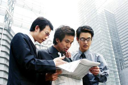 Bespectacled : Three businessmen sharing a newspaper