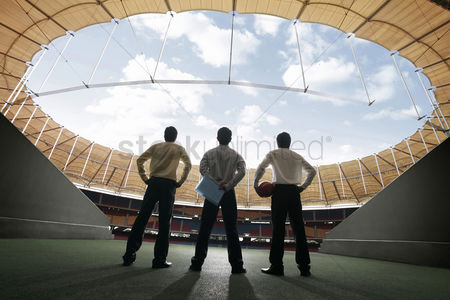 Asian : Three businessmen standing at the stadium