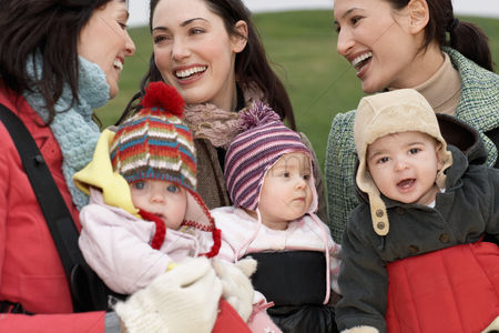 Winter : Three mothers with babies in slings chatting outdoors