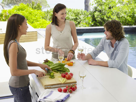 Interior : Three young adult friends preparing a salad while drinking wine and laughing on patio