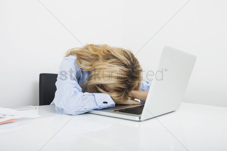Office worker : Tired businesswoman resting head on laptop at office desk