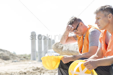 Supervisor : Tired supervisor sitting with colleague at construction site