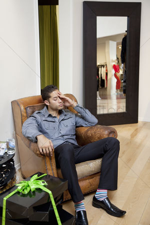 Spending money : Tired young man sitting on armchair in fashion store