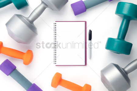 Strong : Top view of dumbbells and notebook on white background with copy space
