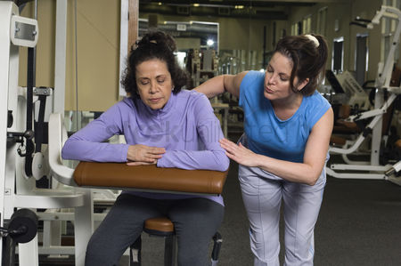 Workout : Trainer assisting senior woman on exercise machine