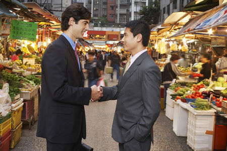 Shopping background : Two business men shaking hands at street market