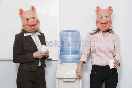 Interior : Two businesswoman in pig masks at a water cooler