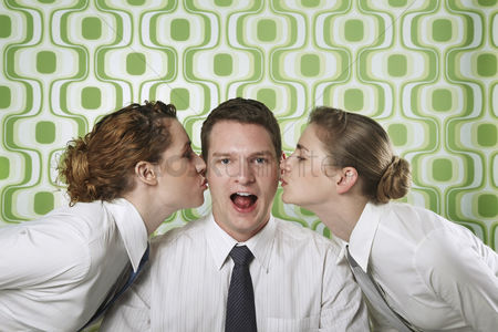 Kissing : Two businesswomen kissing businessman on cheeks
