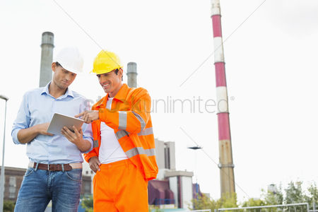 Supervisor : Two construction workers discussing over tablet pc at industry