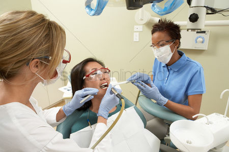 Pain : Two dentists examining female patient in surgery