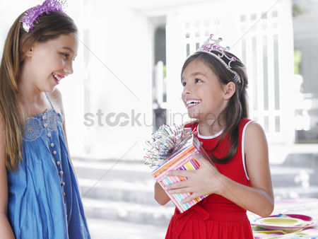 Birthday present : Two girls  7-9 10-12  at birthday party one holding present smiling