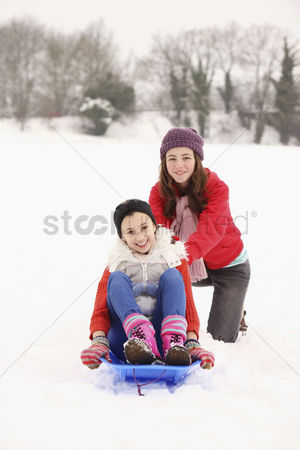Pushing : Two girls playing in the snow  riding sled