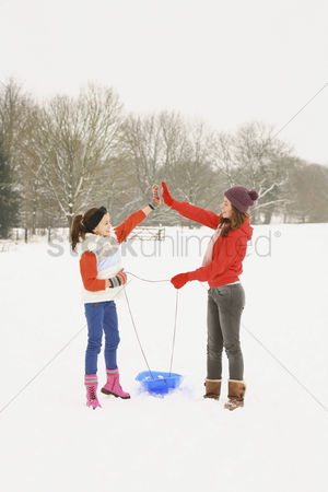 Gladness : Two girls pulling the sled while walking