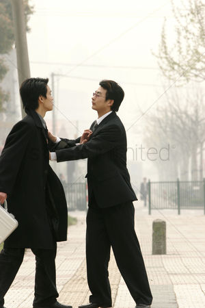 Fight : Two guys in business suit pushing each other