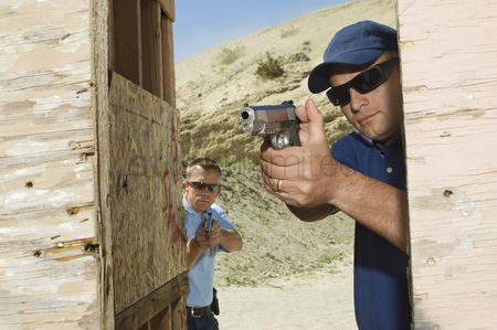 Firing : Two men aiming hand guns at firing range