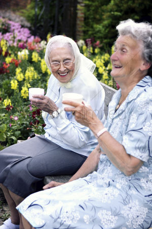 Friends : Two old women sitting on a bench in the park drinking coffee