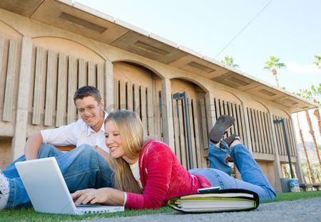 Grass : Two students using laptop outdoors