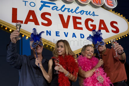 Toasting : Two women and two men posing in front of welcome to las vegas sign group portrait