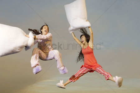 Spirit : Two women having pillow fight mid-air outdoors