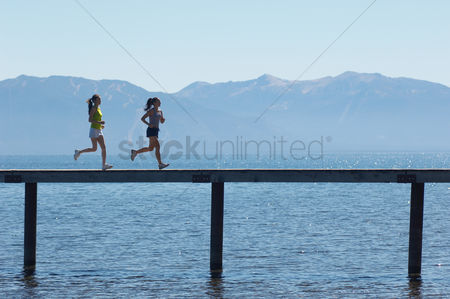 Physical : Two women running along a pier with mountains behind side view