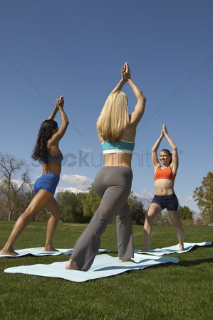 Arm raised : Two young women exercising with instructor in park