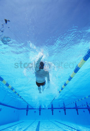 Swimmer : Underwater shot of young male athlete doing backstroke in swimming pool