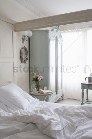 Furniture : Unmade bed in sunlit beamed room