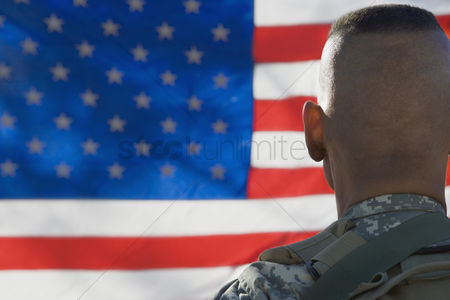 Flag : Us army soldier looking at flag back view